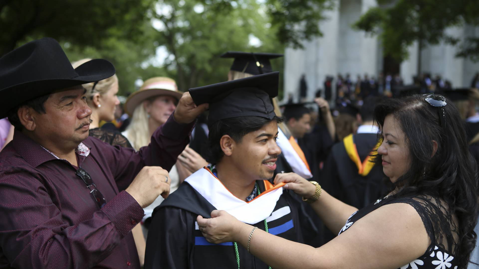 Fidelina Martinez (left) and Juan Leiva (right), natives of El Salvador who live in Trenton, New Jersey, help their son Gerson Leiva (center), the first in his family to go to college, get ready before the processional.