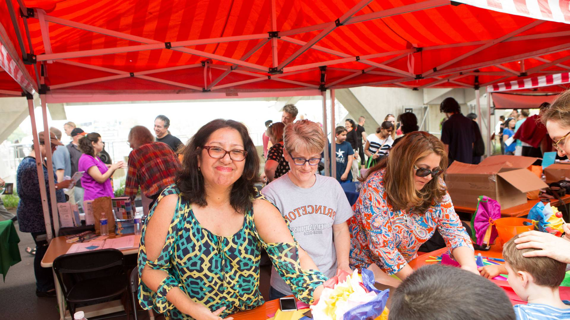 Photo of staff and faculty volunteers helping children at an art booth.