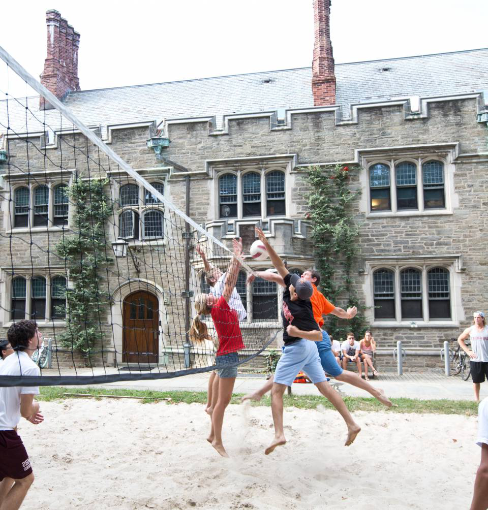 学生们 playing volleyball on sand court