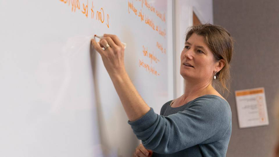 Shana Weber writes on a whiteboard