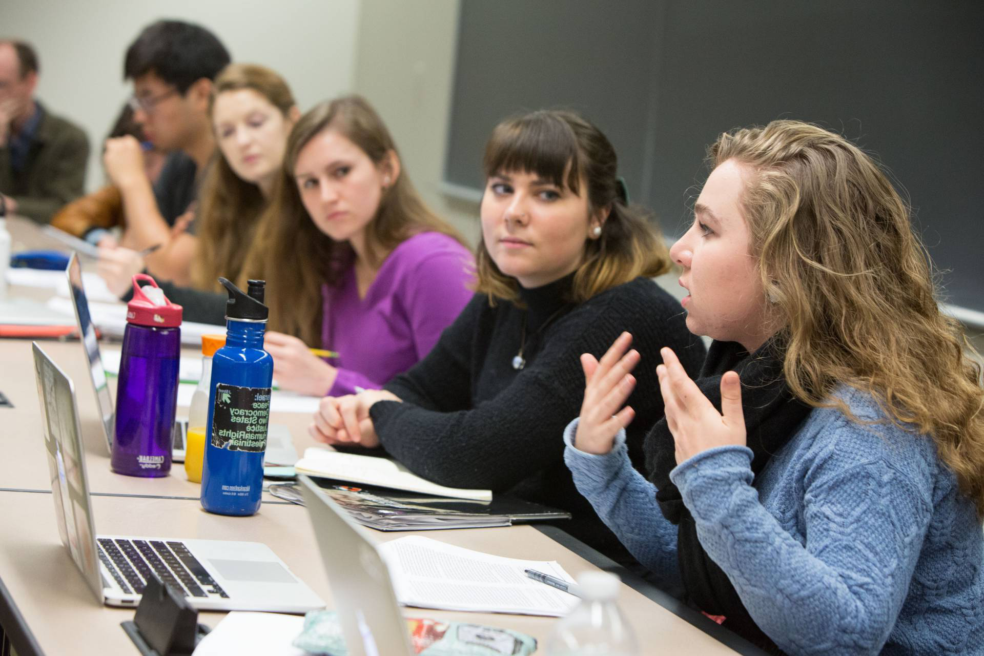 A student makes a point in a discussion with other students around a conference table in a classroom.