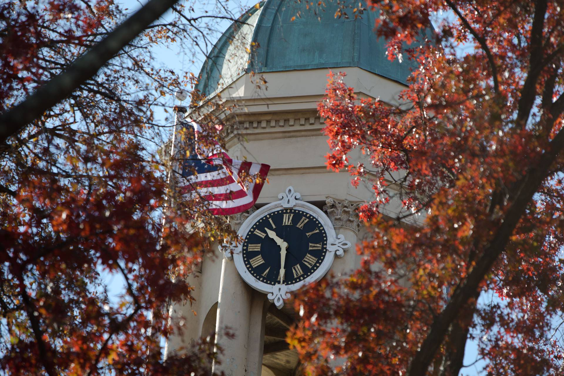 The cupola of Nassau Hall showing its clock and an American flag