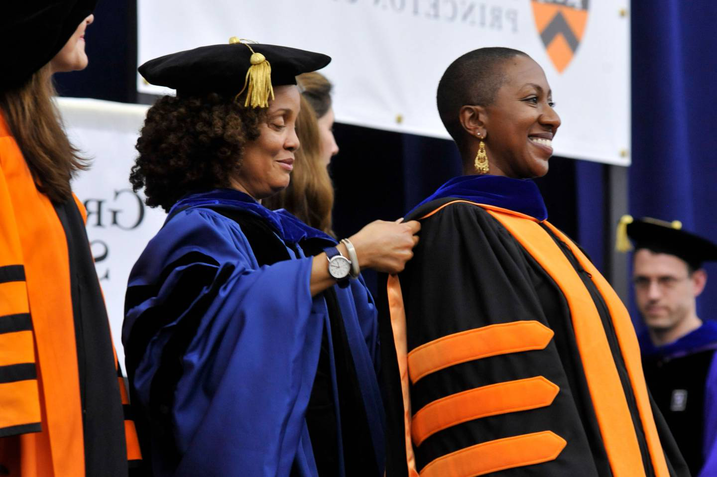 A graduate student is hooded by her adviser