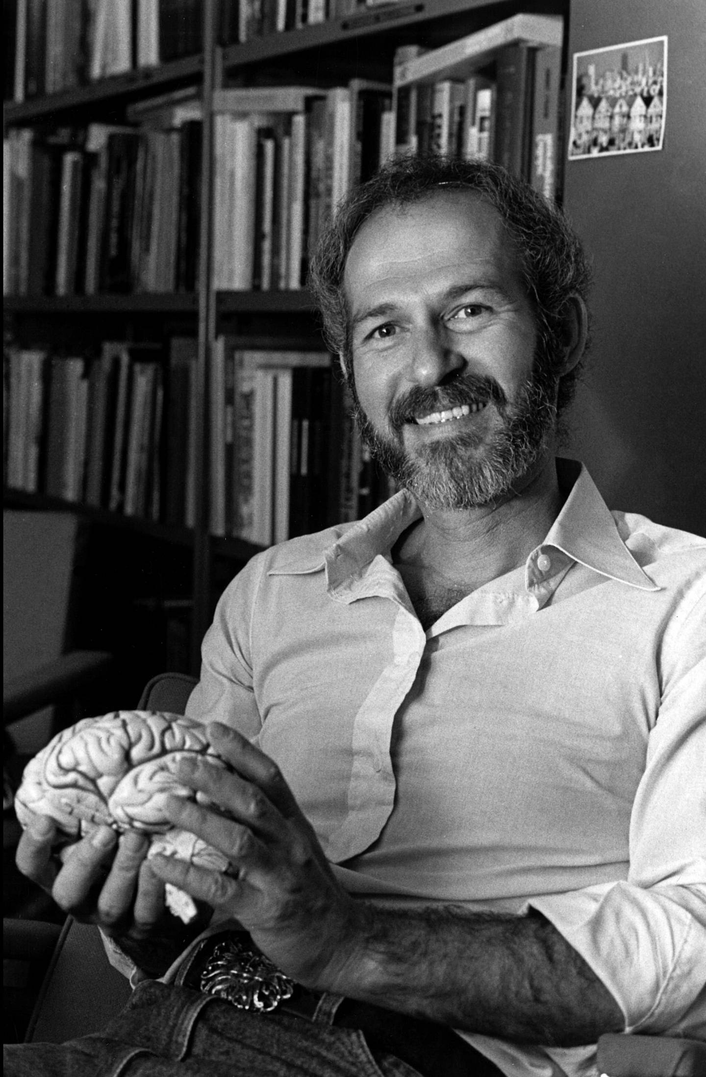 Barry Jacobs holds a model of a human brain